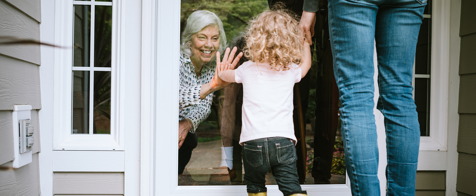 grandmother-seeing-child-through-glass-door