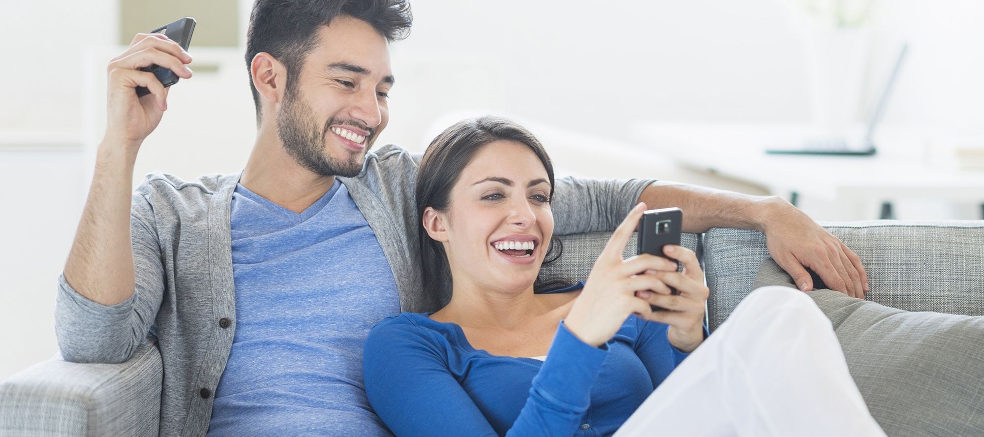 man-and-woman-on-couch-looking-at-phone