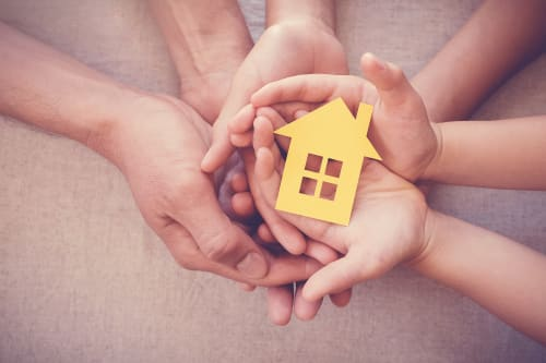family-holding-house-in-hands